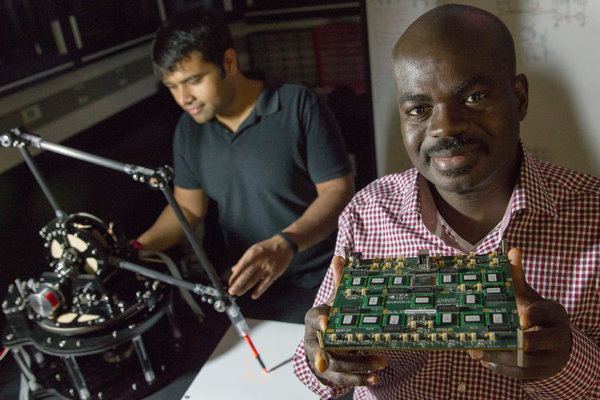 Stanford University computer scientists Kwabena Boahen holds a brain-like processor attached to a robotic arm | Image credit: Erin Lubin / The New York Times