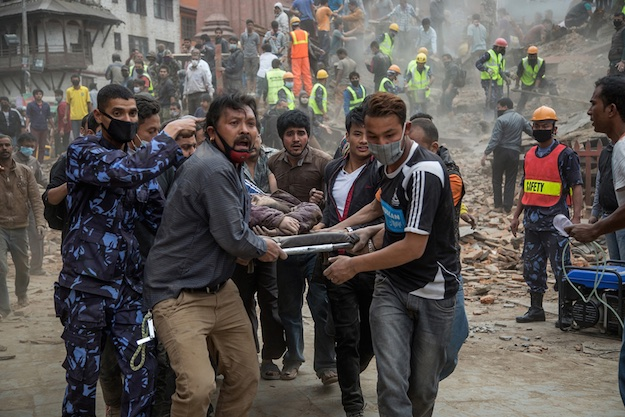 KATHMANDU, NEPAL - APRIL 25: Emergency rescue workers carry a victim on a stretcher after Dharara tower collapsed on April 25, 2015 in Kathmandu, Nepal. More than 100 people have died as tremors hit Nepal after an earthquake measuring 7.9 on the Richter scale caused buildings to collapse and avalanches to be triggered in the Himalayas. Authorities have warned that the death toll is likely to be much higher. (Photo by Omar Havana/Getty Images)