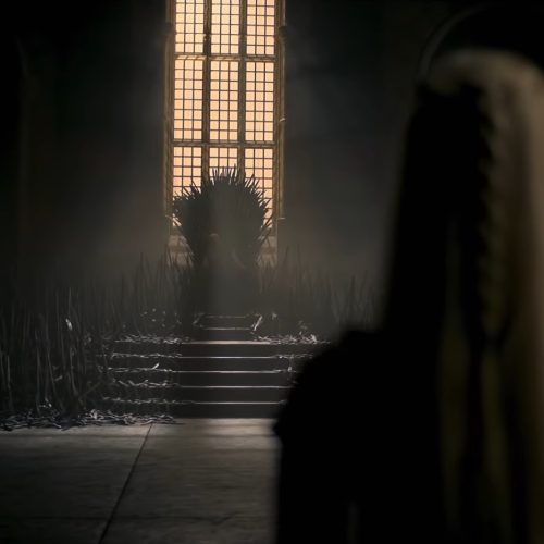 A woman with long blond hair admires the Iron Throne