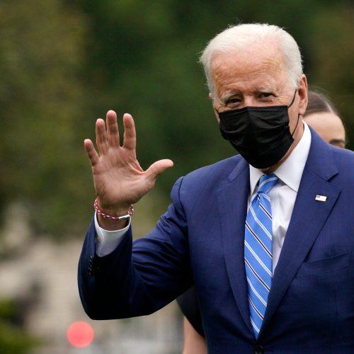 President Joe Biden waving to hecklers shouting Let's go Brandon!
